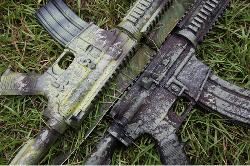camo painted gun in grass